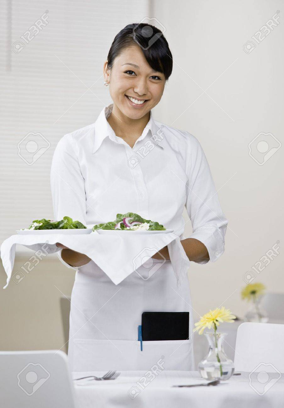 young female server tray of food standing next to table stock photo young female server tray of food standing next to table vertically framed shot