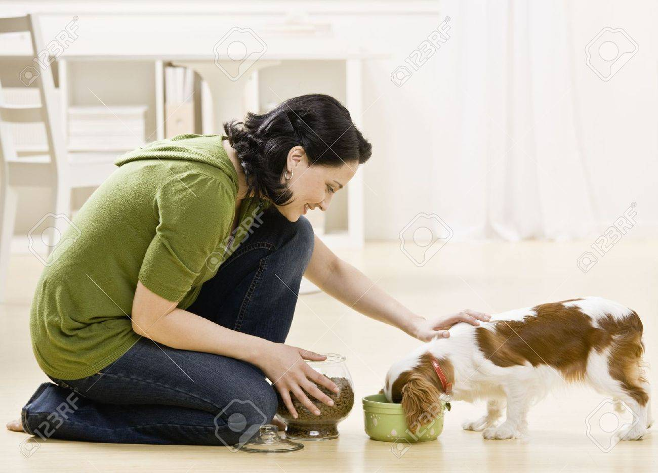 woman feeding and petting puppy
