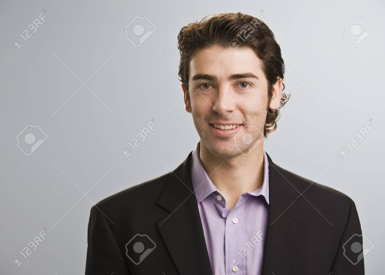 A young businessman is standing in a room and smiling at the camera.  Horizontally framed shot. Stock Photo - 6413788