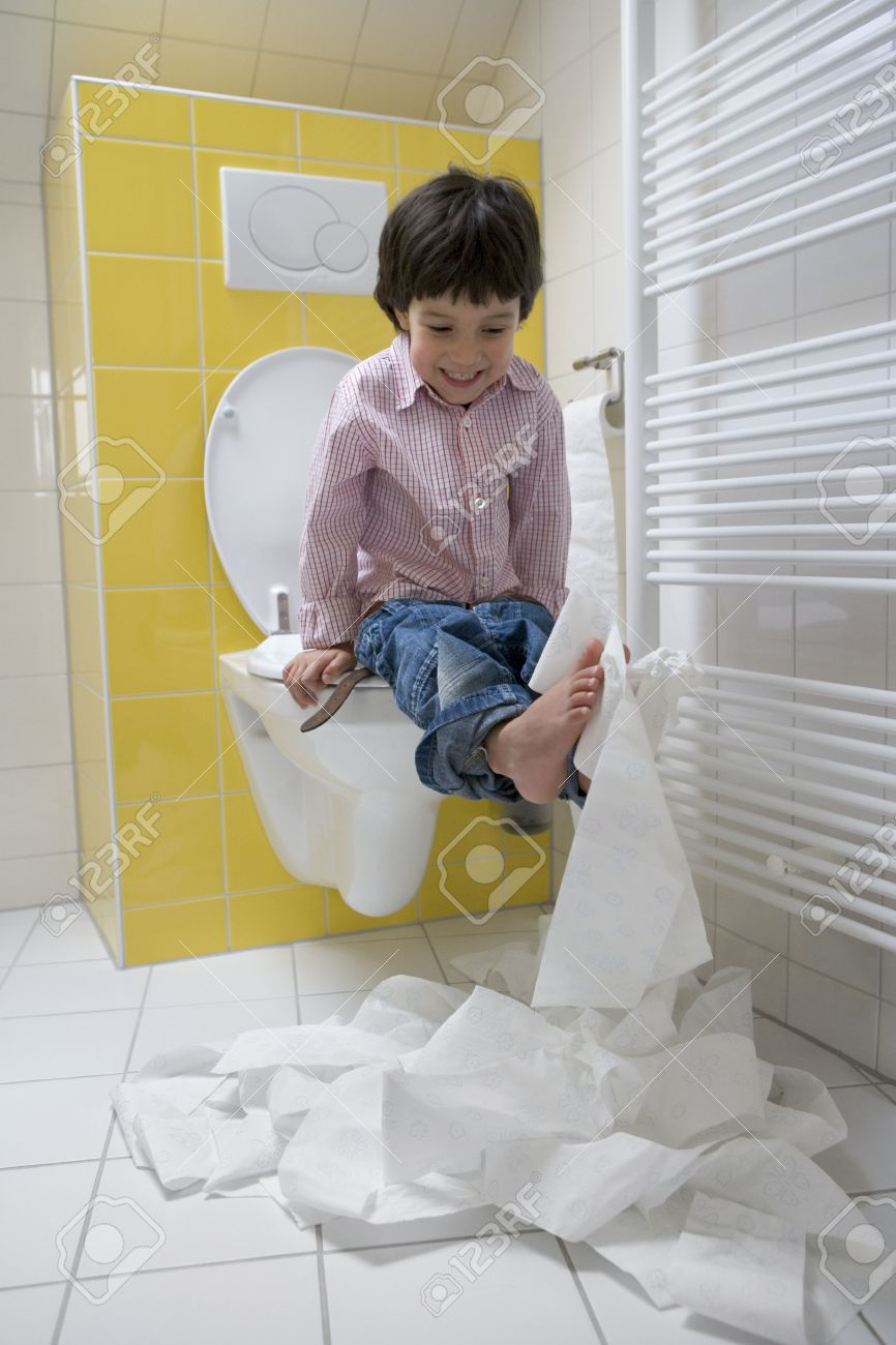 young boy and the toilets Stock Photo - Little boy makes a mess with toilet paper in the bathroom