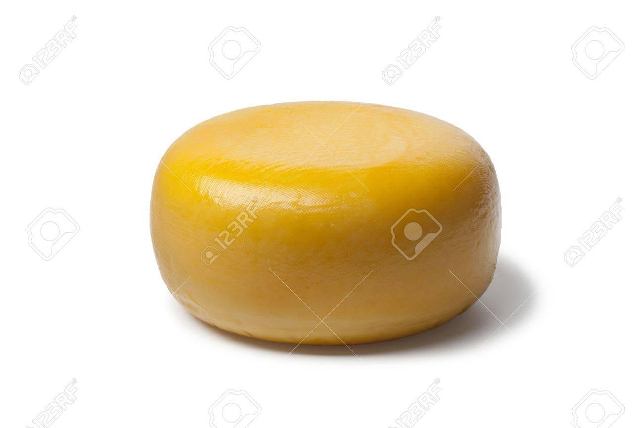 Whole yellow Dutch Gouda cheese on white background - 13598090