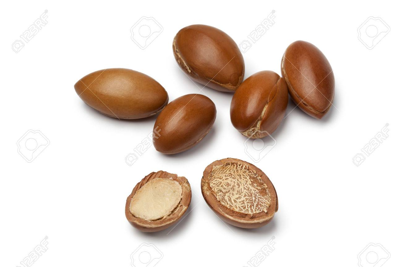 Whole and half Moroccan Argan nuts on white background - 23215288