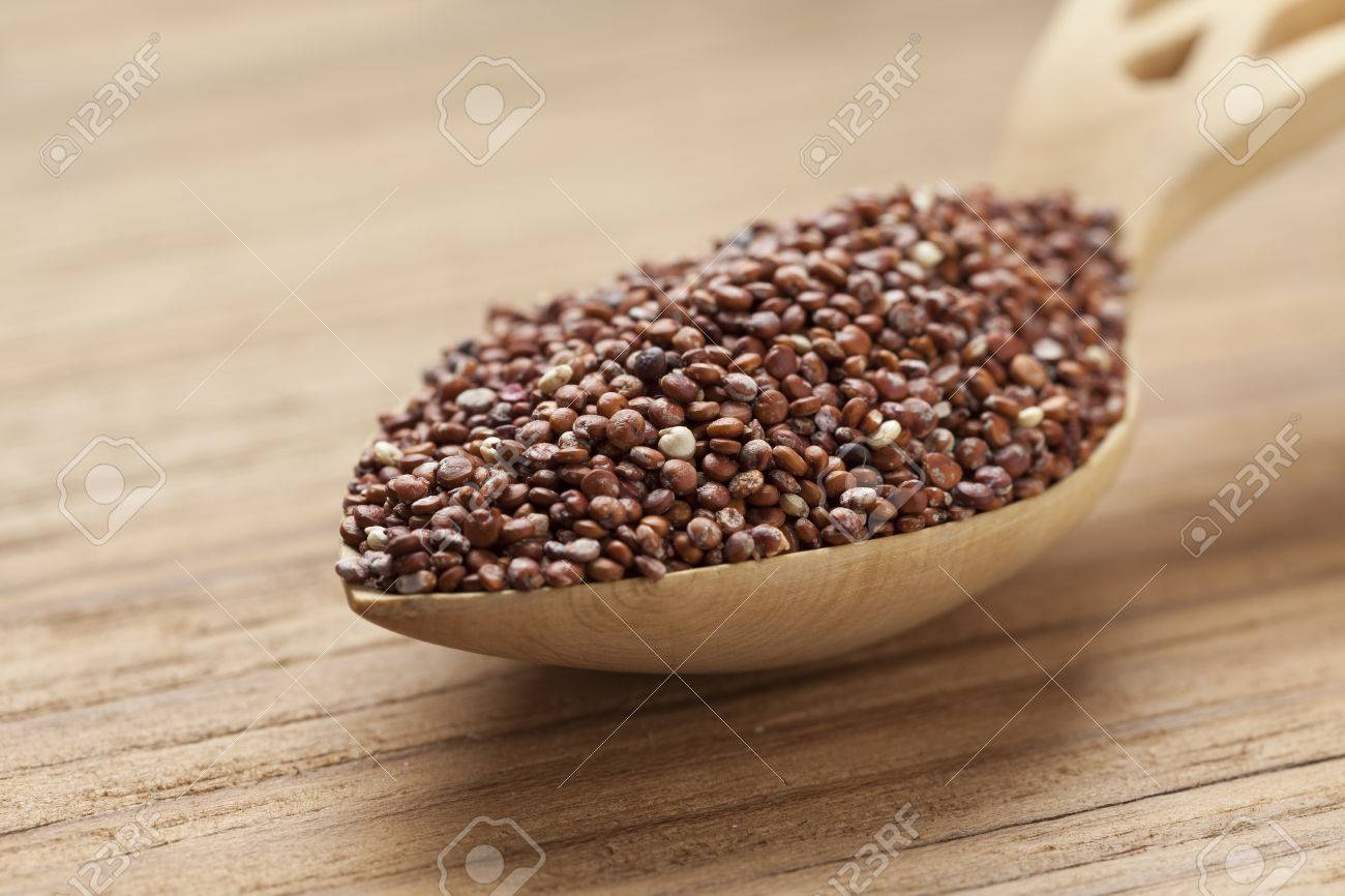 Red raw Quinoa seeds on a wooden spoon - 44875497