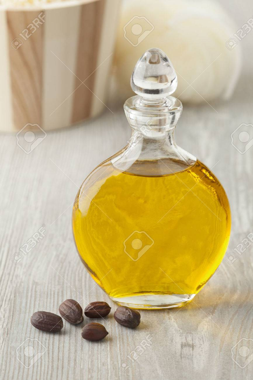 Bottle of cosmetic Jojoba oil and seeds - 60410345