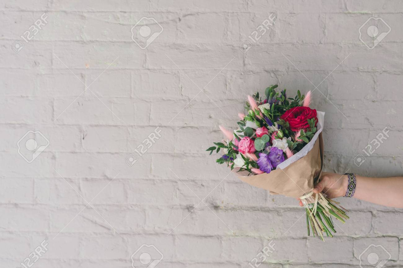 Stylish bouquet of fresh flowers against brick wall composition stock photo stylish bouquet of fresh flowers against brick wall composition from freesia roses eucalyptus leaves in hand with free space for text izmirmasajfo