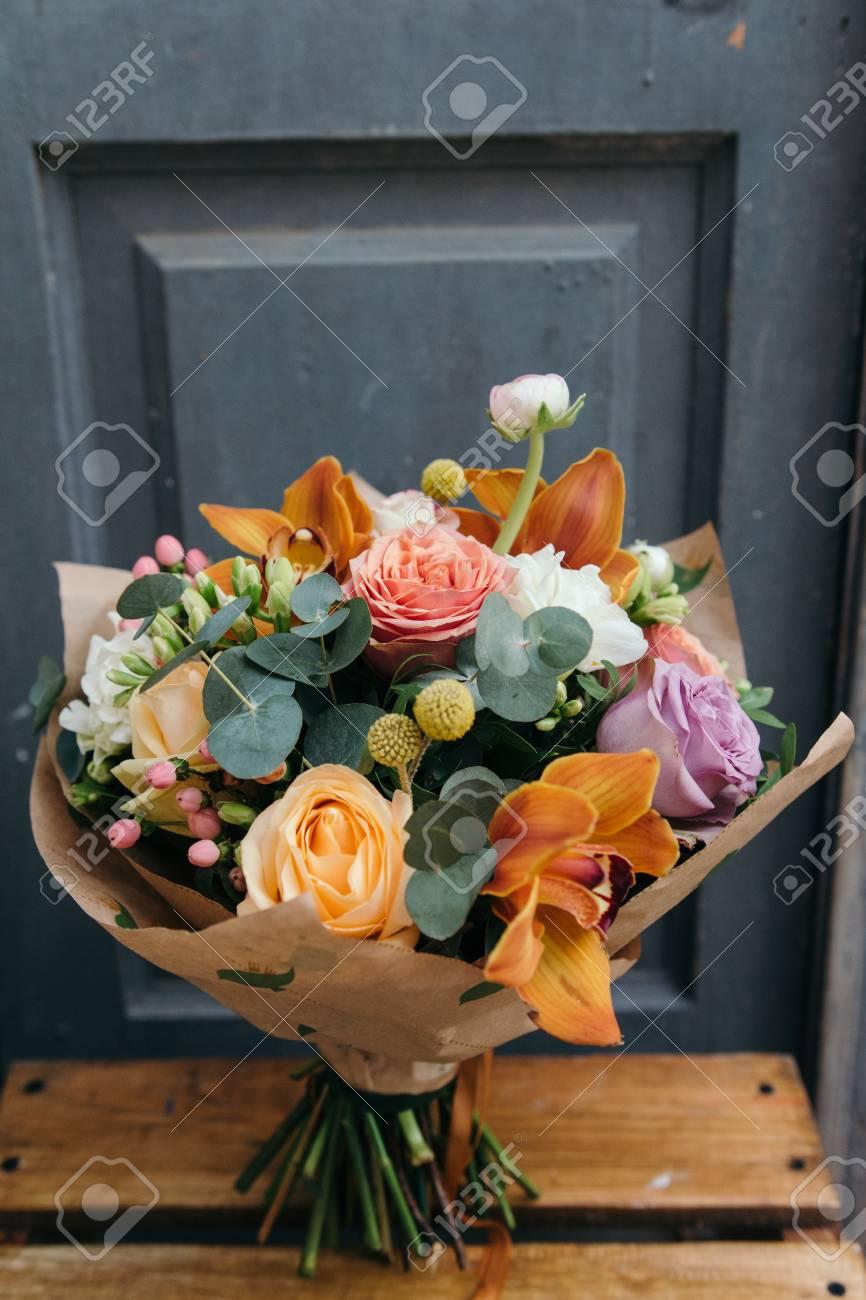 Feuille D Eucalyptus Bouquet bouquet coloré de différentes fleurs fraîches contre le mur de briques.  bouquet d'orchidées, de roses, de freesia et de feuilles d'eucalyptus. fond  de