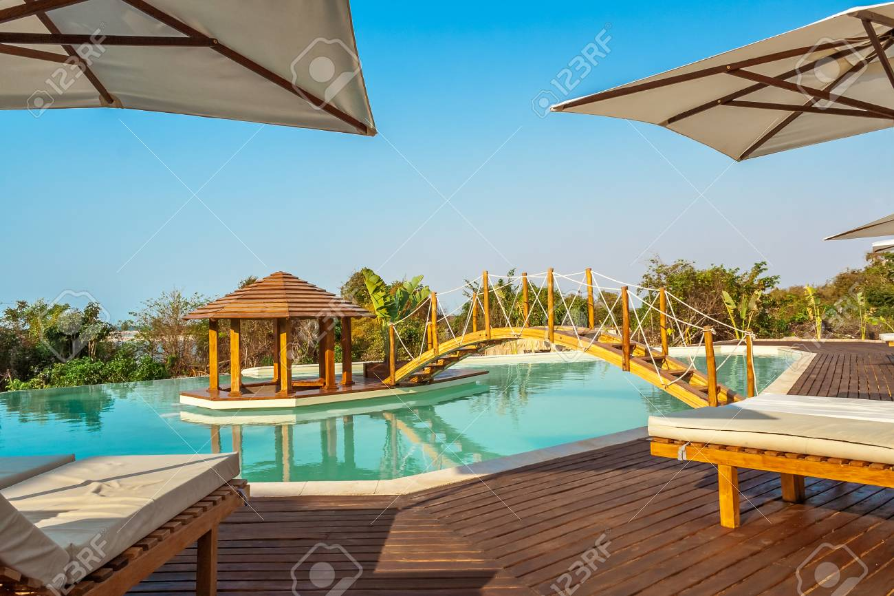 luxury swimming pool with a wooden bridge and central bar