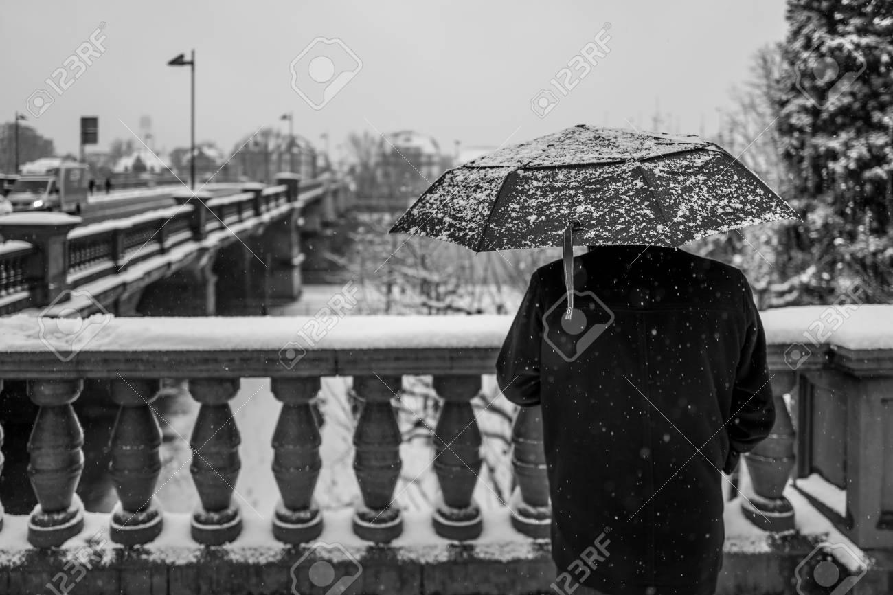 Rear view of man with umbrella in snowy Frankfurt Standard-Bild - 91750258