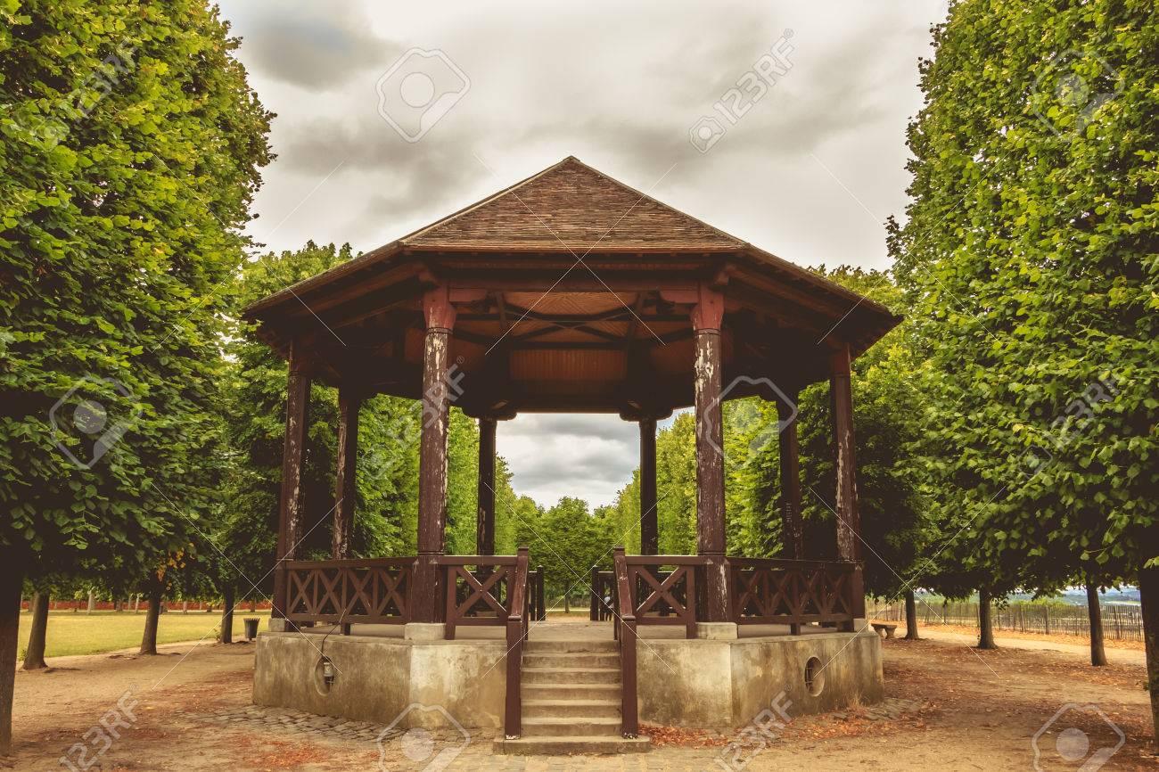 Kiosque de musique en bois authentique porté sous un ciel gris dans un  jardin français