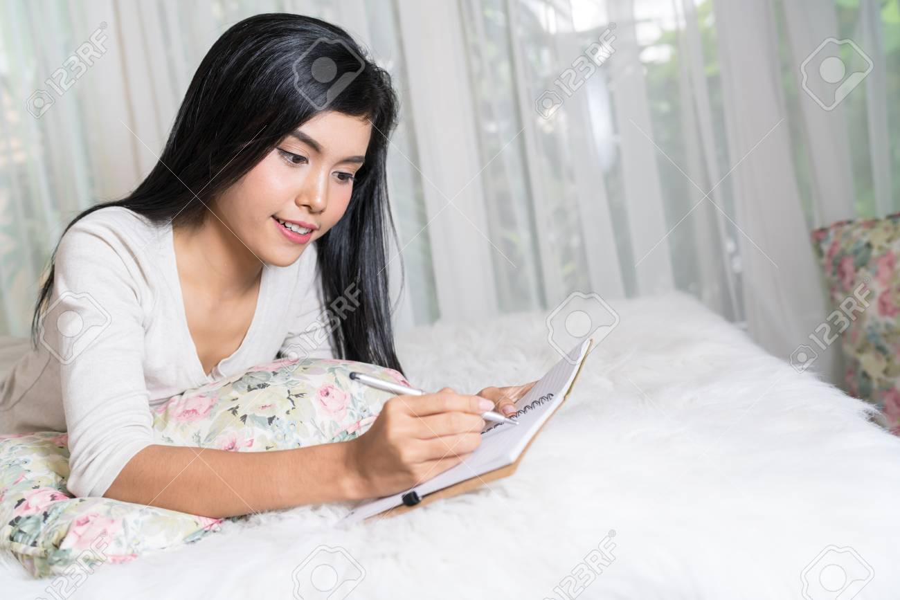 asian woman writing in journal in bed in the bedroom. stock photo