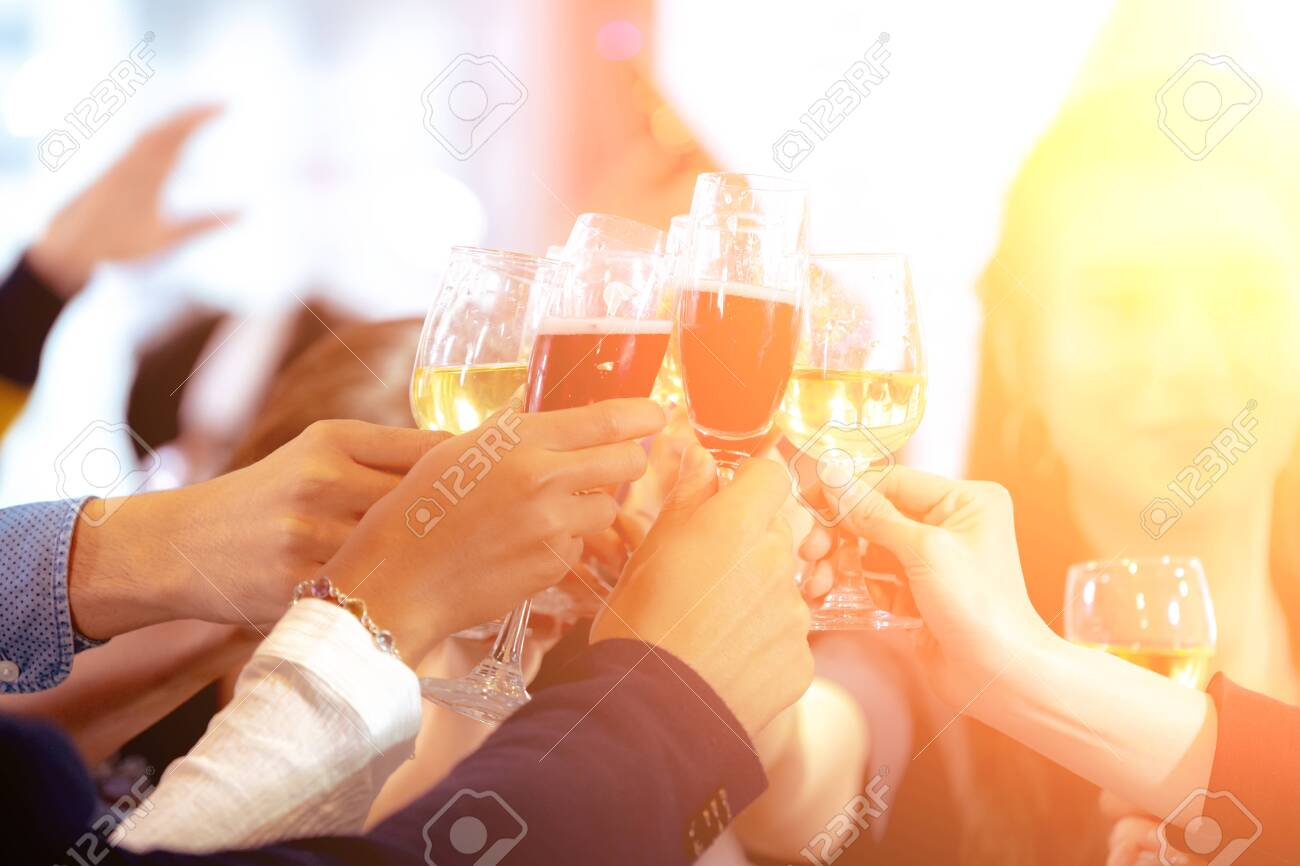 Close up Clinking Glasses of Champagne or Wine. Group of Business People Celebrating New Year at Office party. Friends Happily Organized a celebration Party and Cheers Together at Workplace. - 140706339
