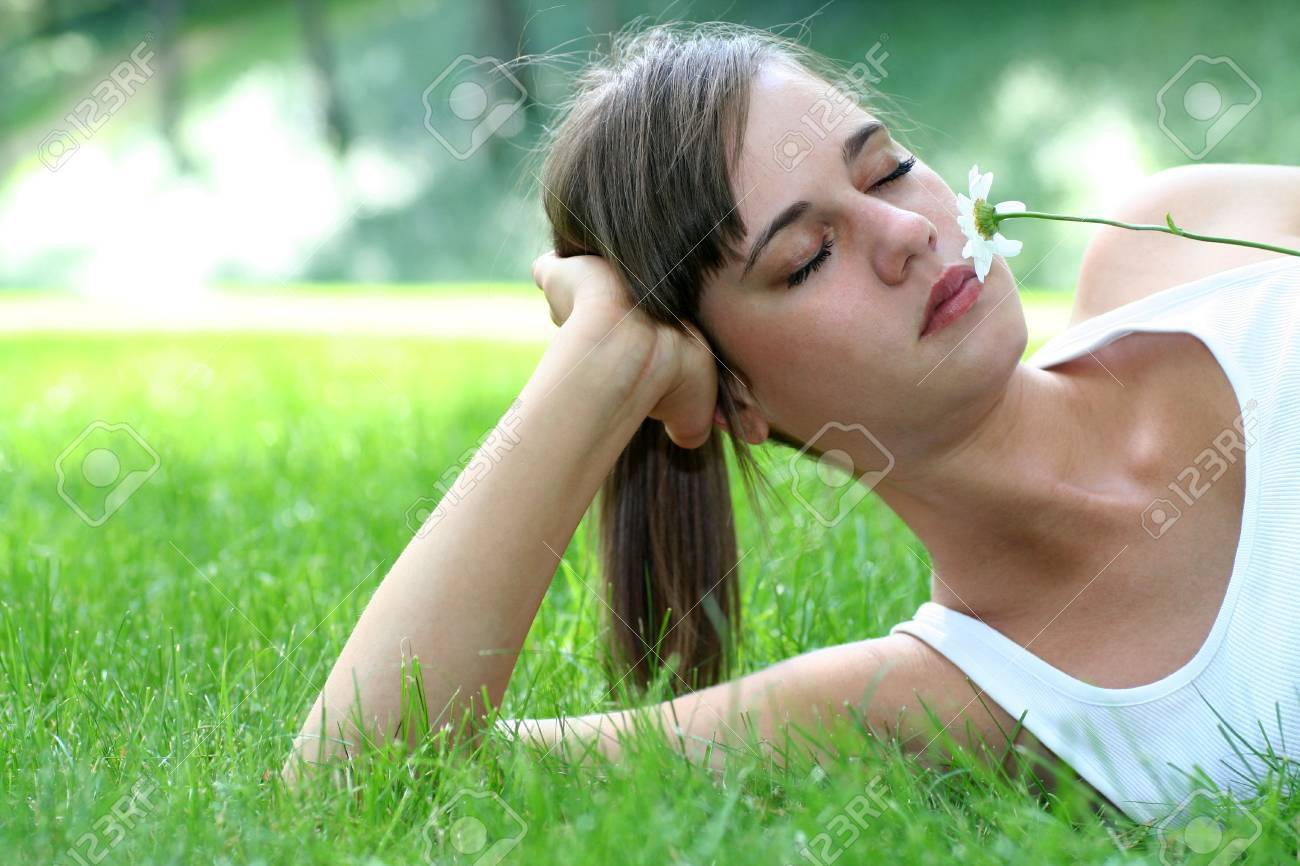 woman lying on a lawn smelling a flower Stock Photo - 1328466