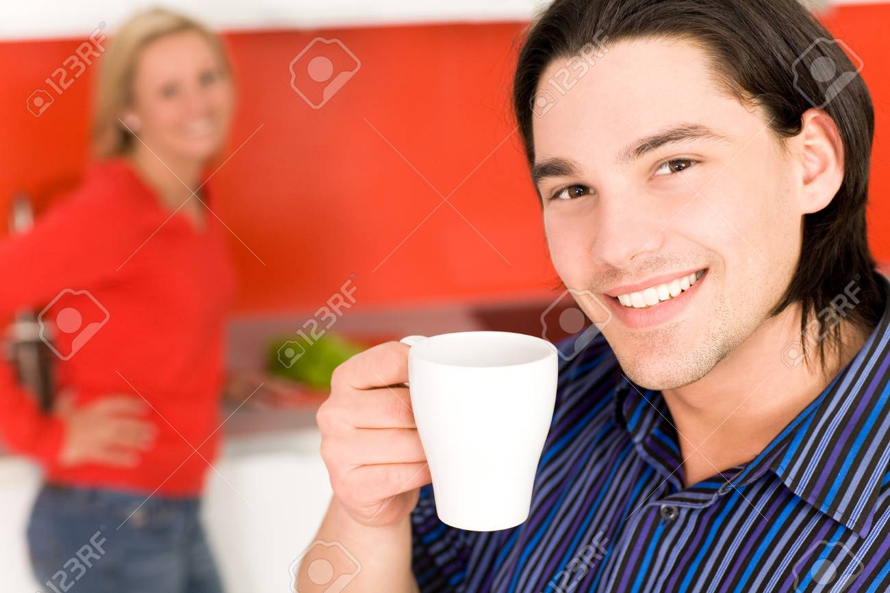 Couple in kitchen, man holding coffee cup Stock Photo - 4504034