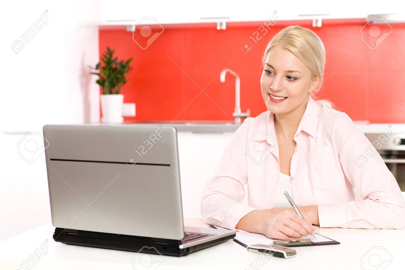Woman using laptop in kitchen Stock Photo - 4599084