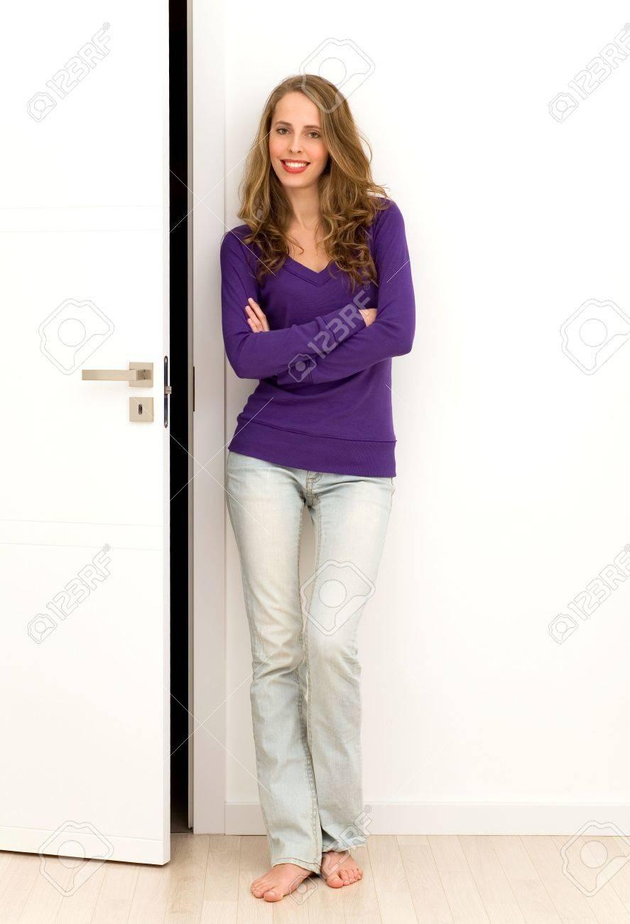 Stock Photo - Woman standing next to door