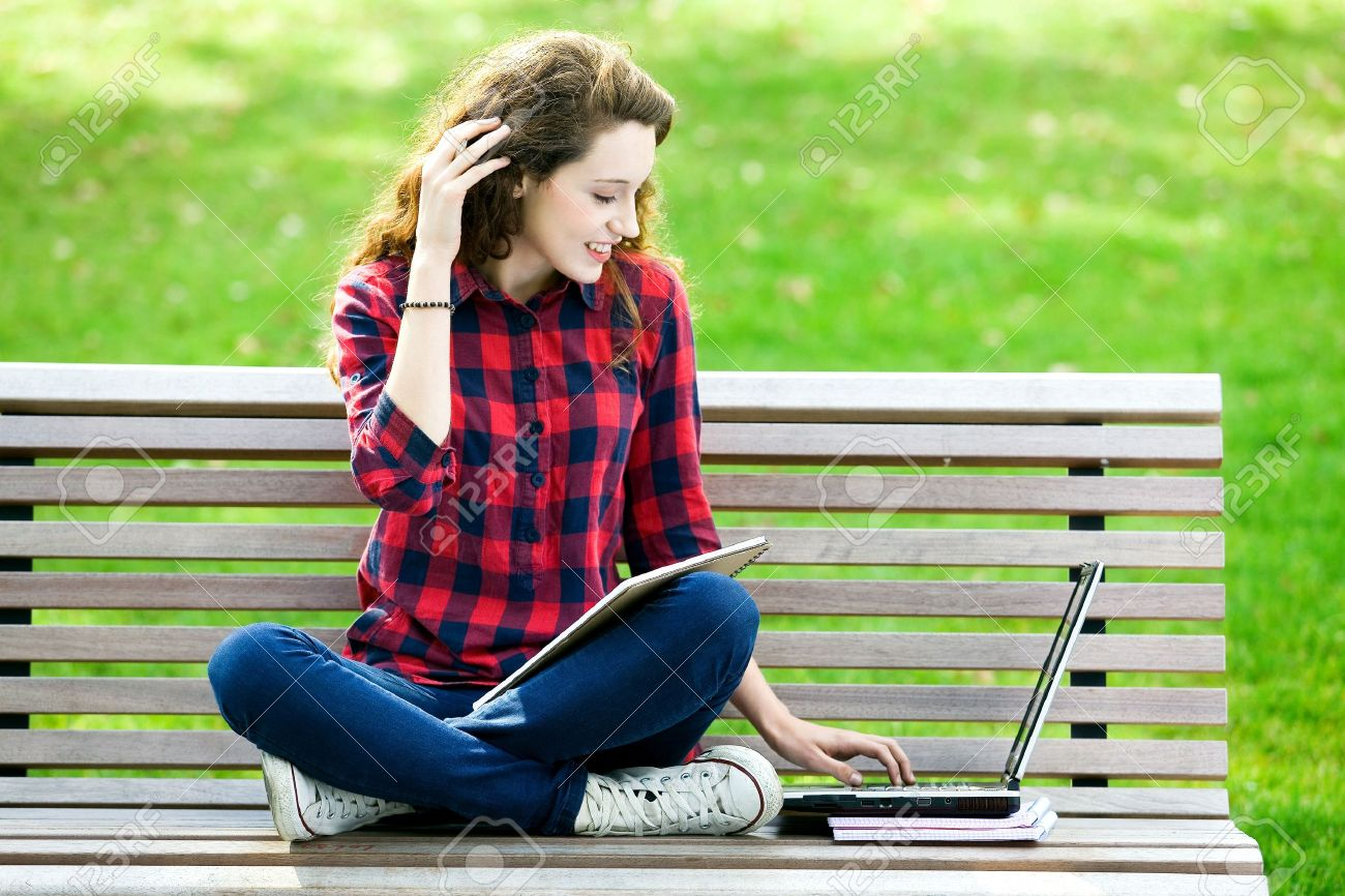 Girl using a laptop on a bench - 10567599
