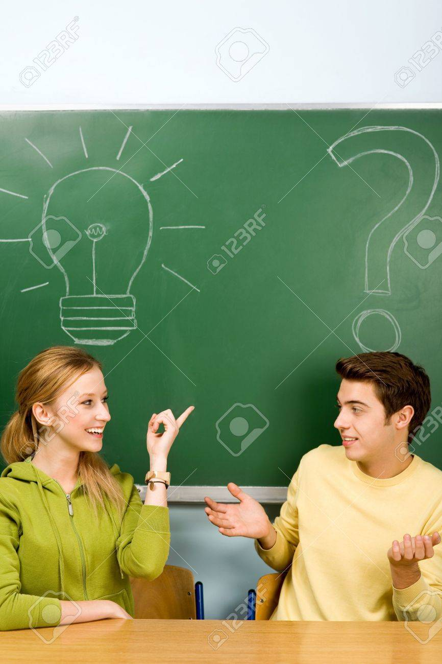 Two students with light bulb and question mark on chalkboard Stock Photo - 11195104