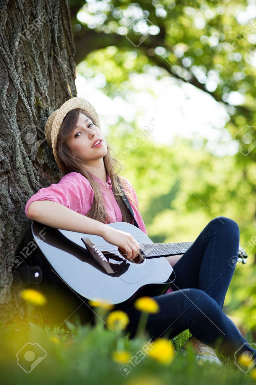 Woman playing guitar in park Stock Photo - 13756749