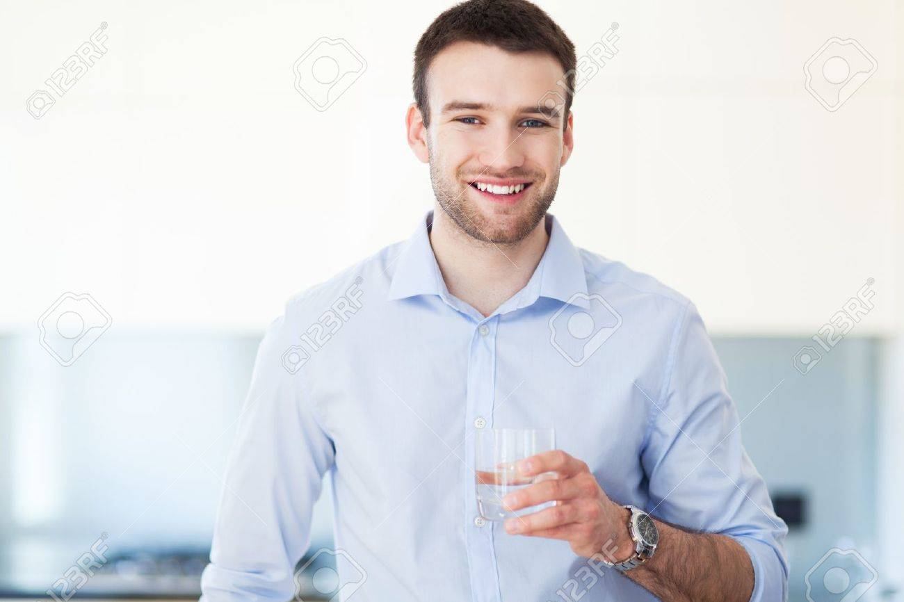 Man in kitchen with glass of water Stock Photo - 19399901