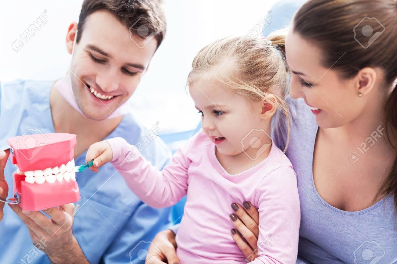 Dentist teaching girl how to brush teeth - 24638997