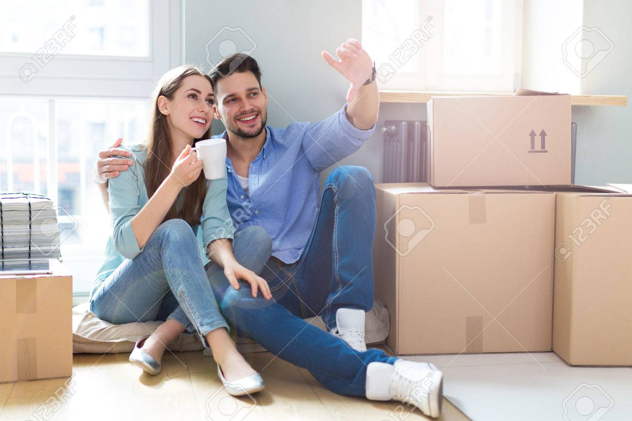 Couple on floor next to moving boxes - 55951861