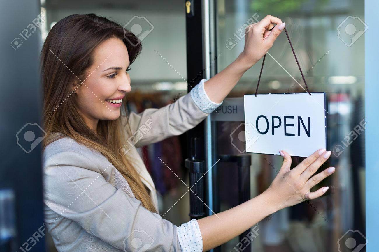 Woman hanging open sign on door - 57518693