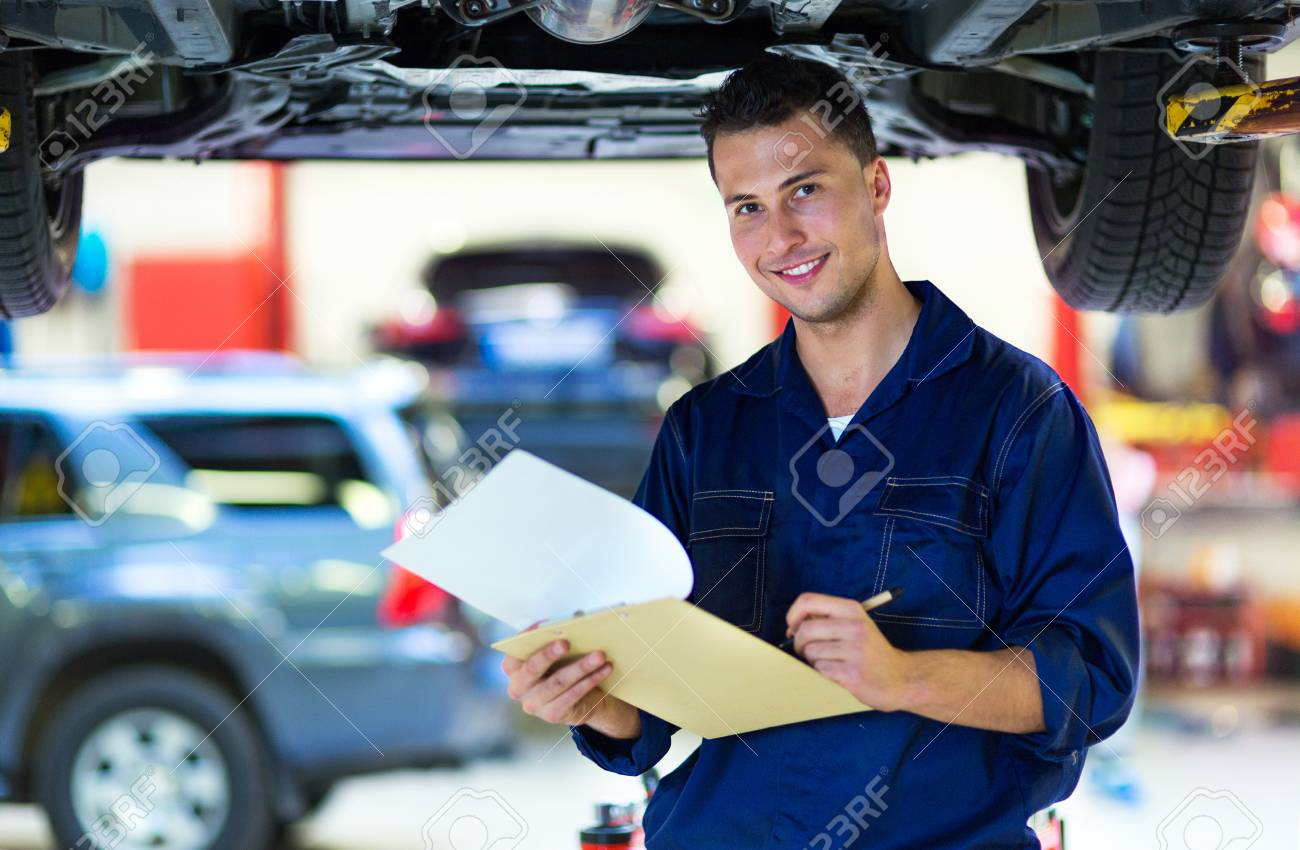 Mechanic working on car in auto repair shop - 91013926