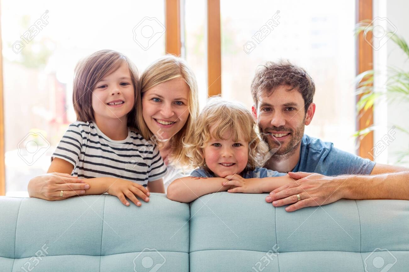 Happy young family with two children at home - 124427731