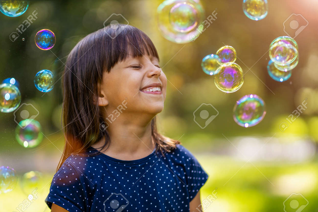 Girl playing with soap bubbles outdoors - 154910199