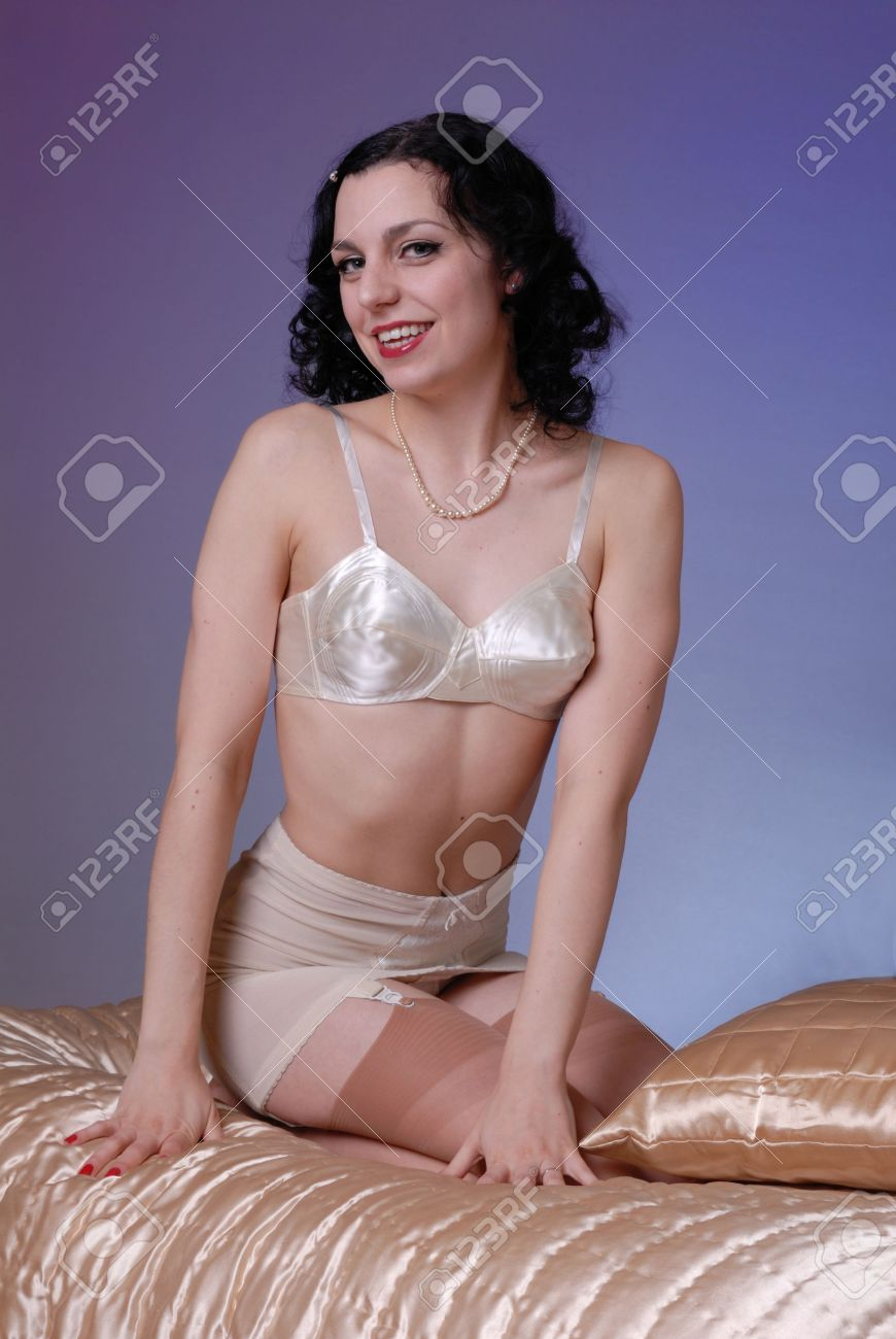 97ac20ea7 Retro fifties pin-up attractive girl in vintage satin bra and girdle in  boudoire