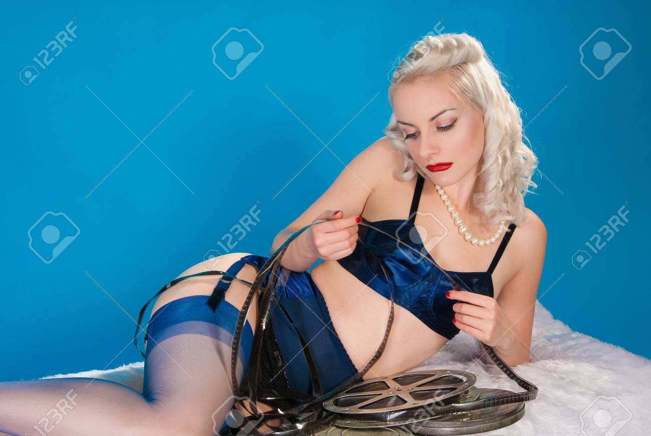 f95af6f2b Fifties pinup in vintage lingerie checking film reels Stock Photo - 23923744