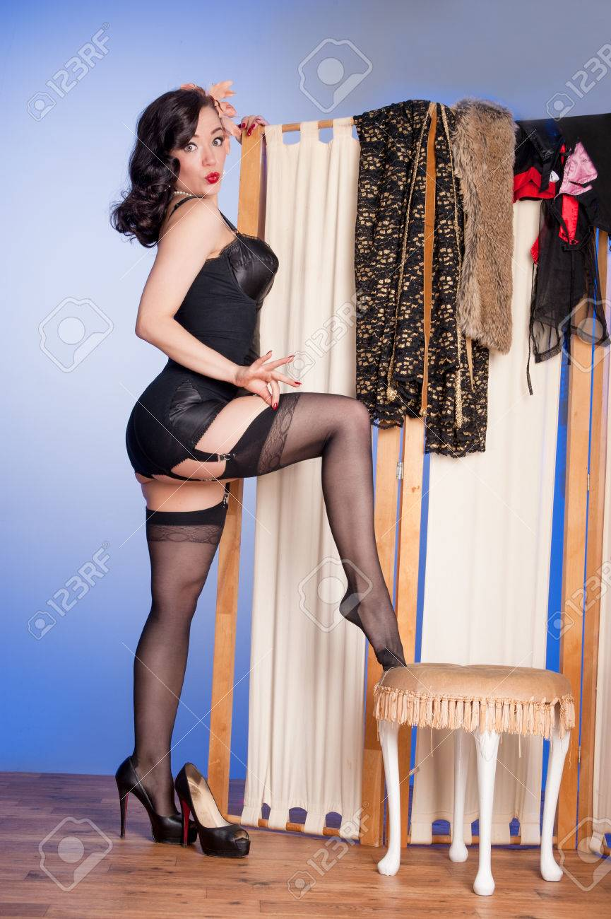 8e88cd7bada Cute pinup in black lingerie adjusts her stockings in boudoir