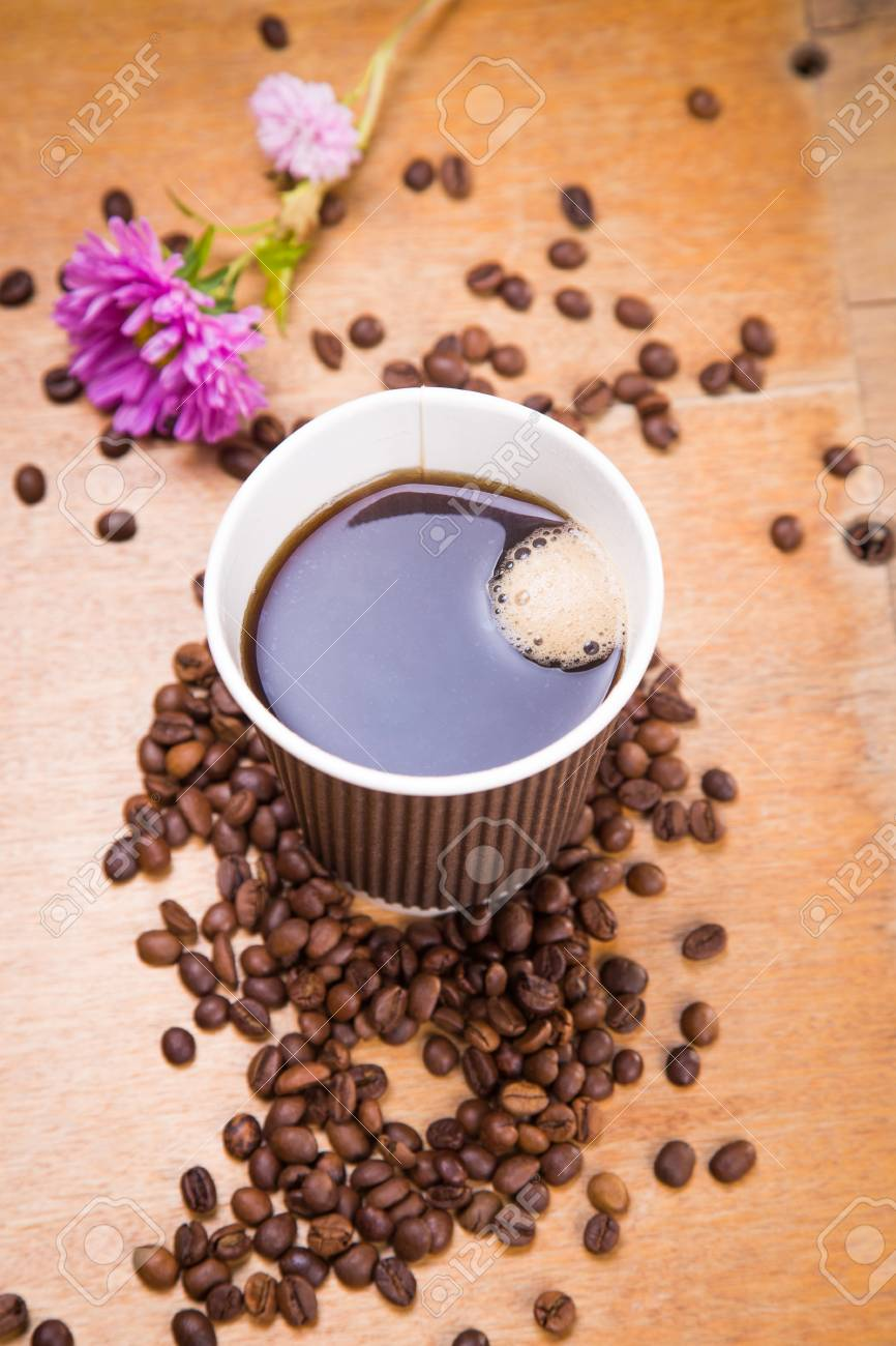 Fresh Hot Coffee In Paper Brown Container With Seeds And Flower