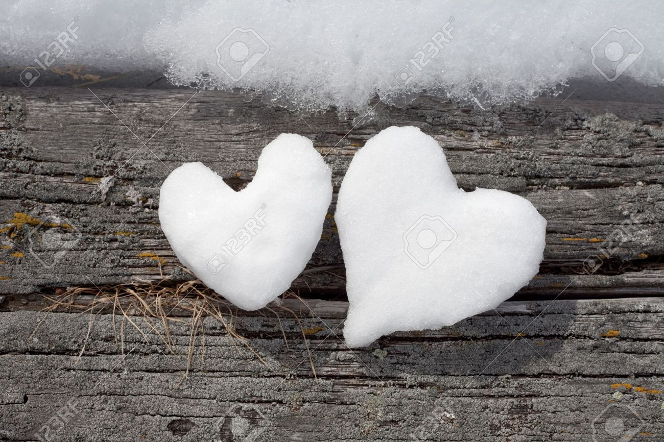 Two Valentine's Day Hearts formed from snow on weathered timber surface. Stock Photo - 7288183