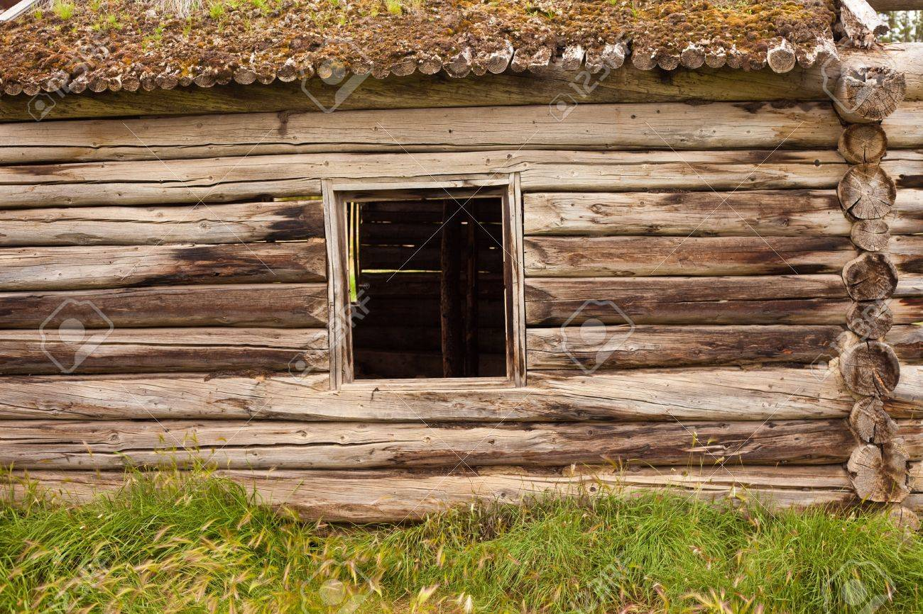 Historic Log House Wall With Glassless Window Frame And Earth Roof. Stock  Photo