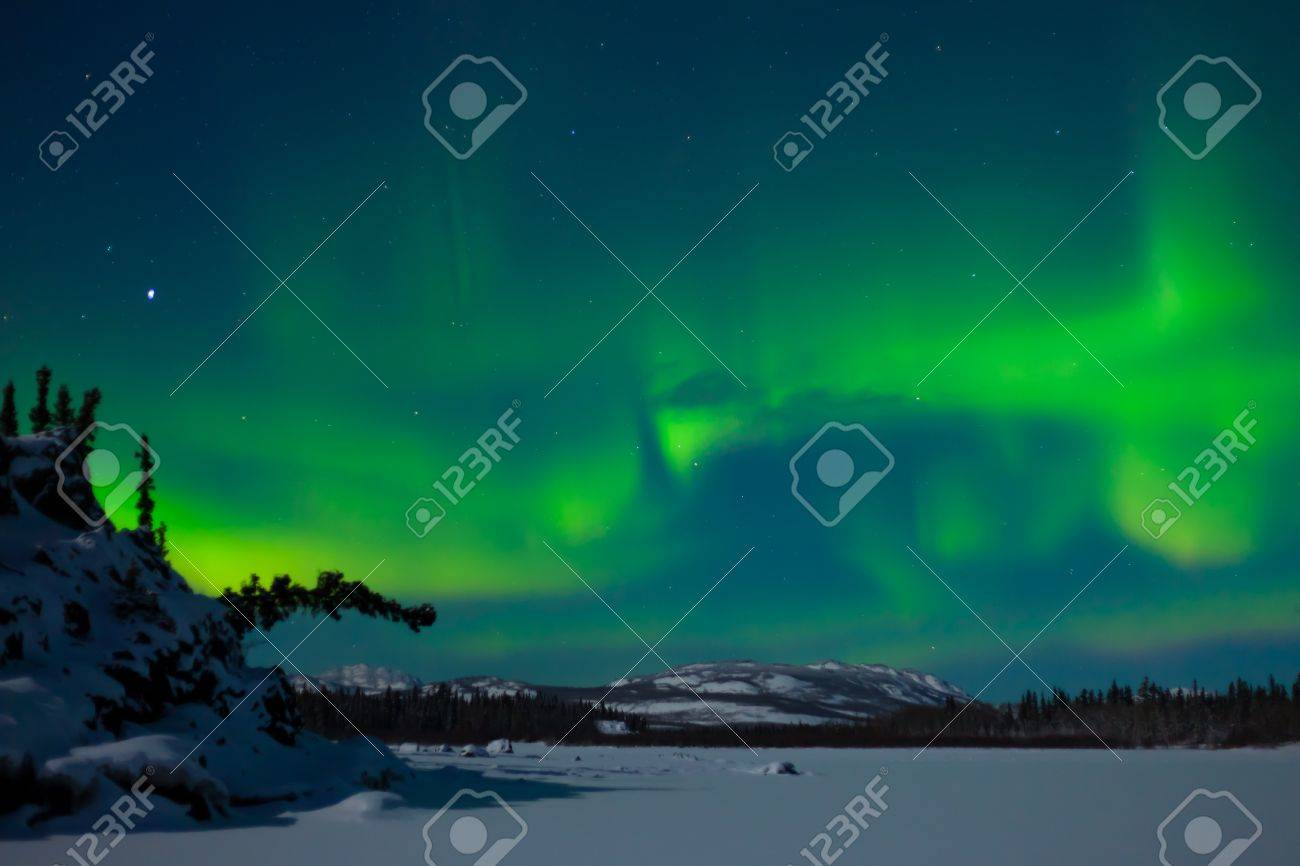 Northern Lights (Aurora borealis) over moon lit snowscape of frozen lake and forested hills. Stock Photo - 8636491