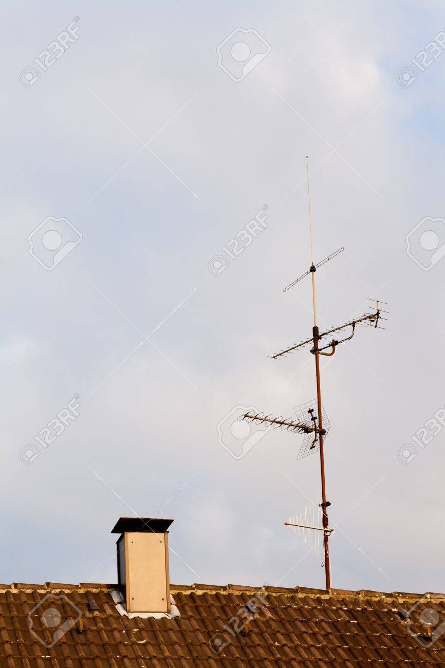 Old-fashioned analogue tv antenna on ceramic shingle rooftop. - 10097660