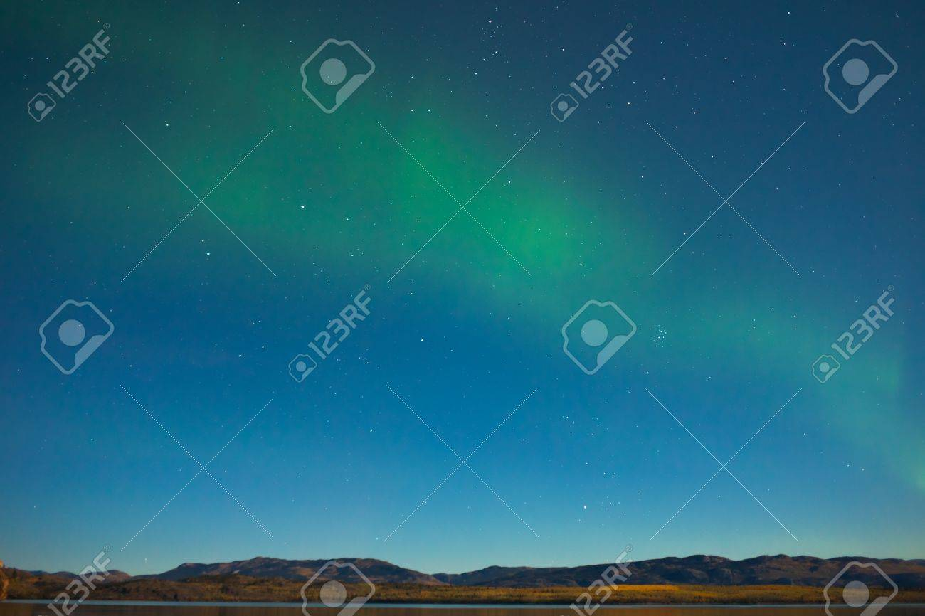 Northern lights (Aurora borealis) in moonlit night over Lake Laberge, Yukon, Canada, in fall. Stock Photo - 10671496