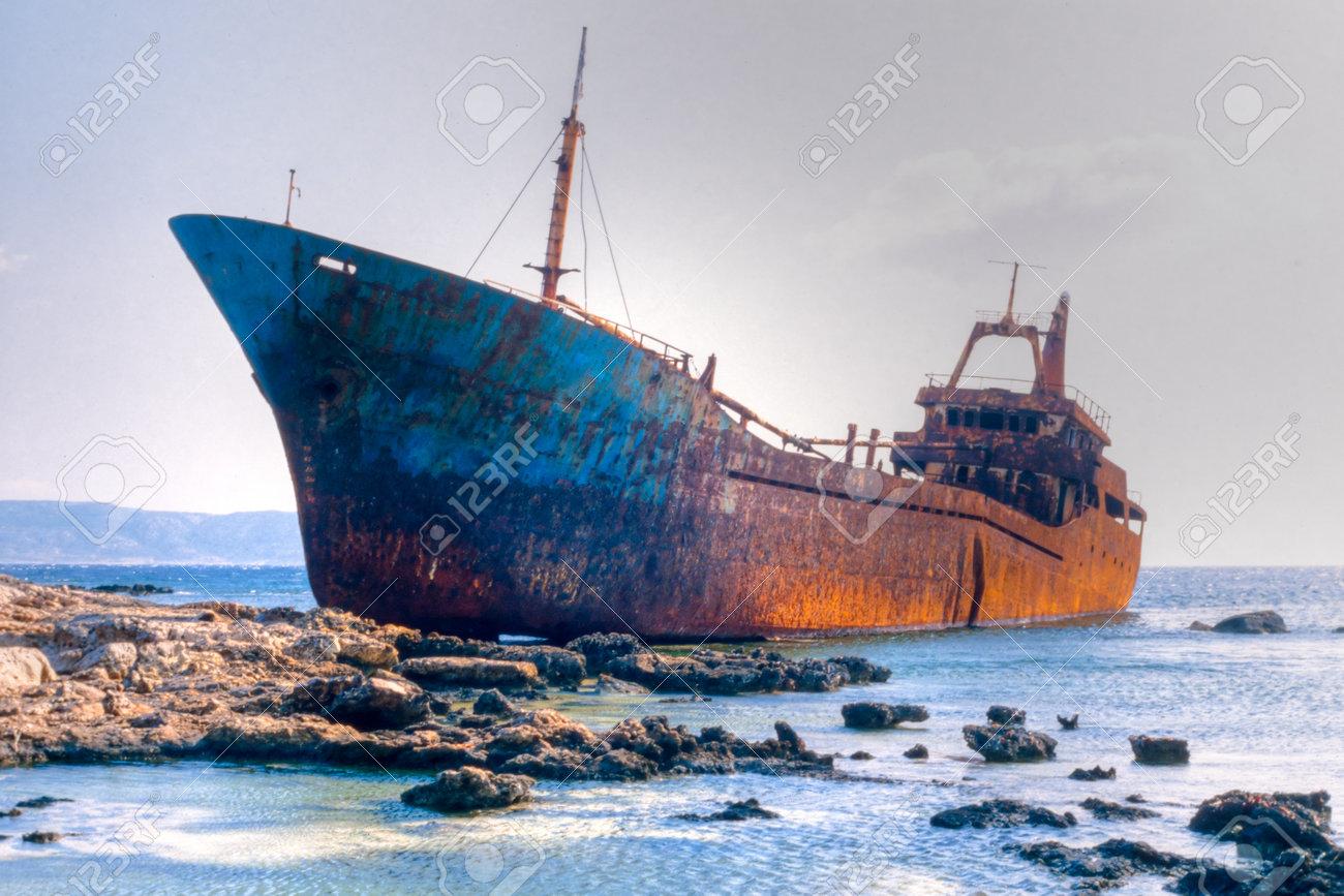 Abandoned broken ship-wreck beached on rocky sea shore. Stock Photo - 14145206
