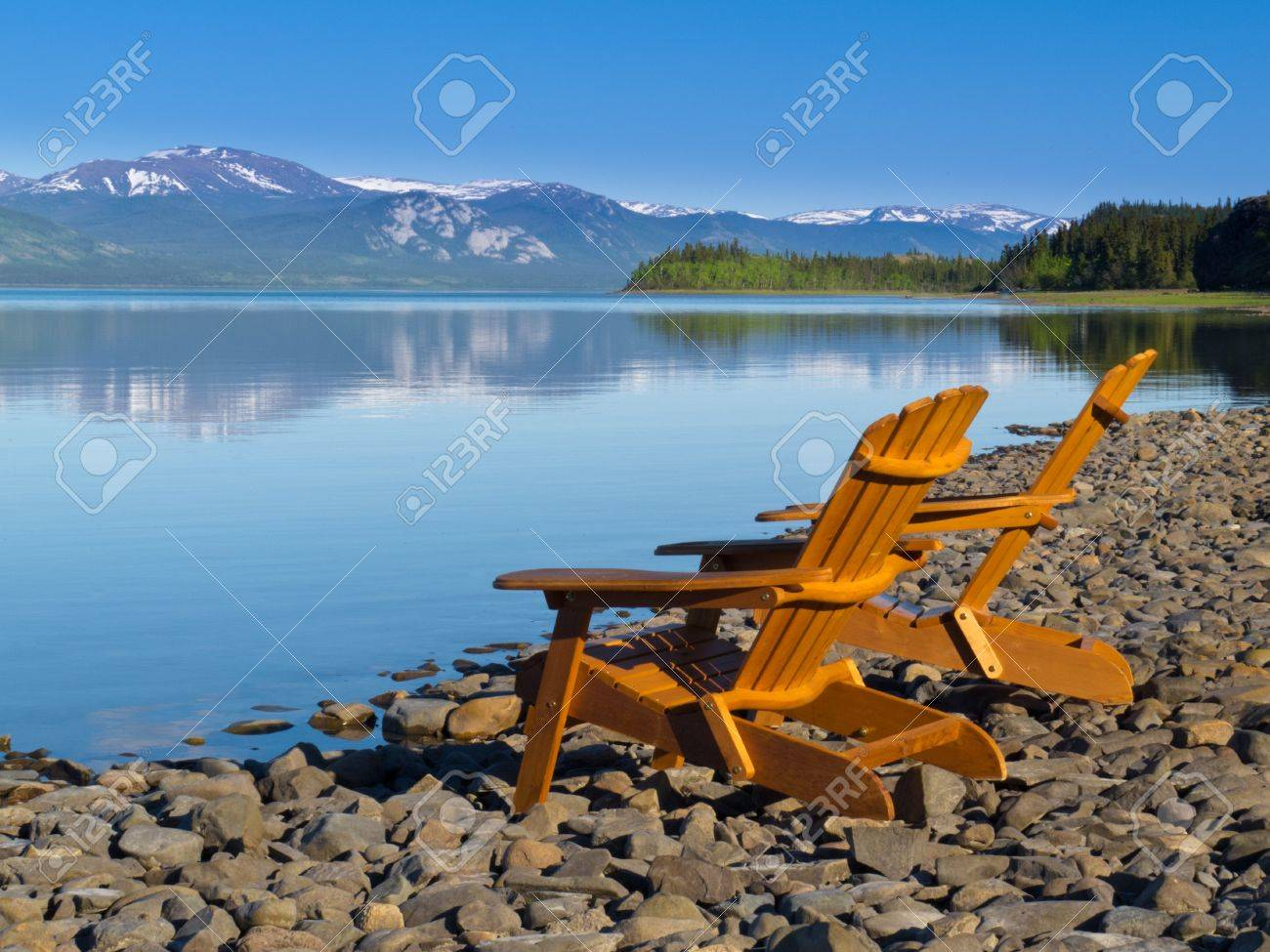 Delightful Two Empty Wooden Adirondack Chairs Or Muskoka Deckchairs On Stony Shore  Overlooking Scenic Calm Lake Laberge