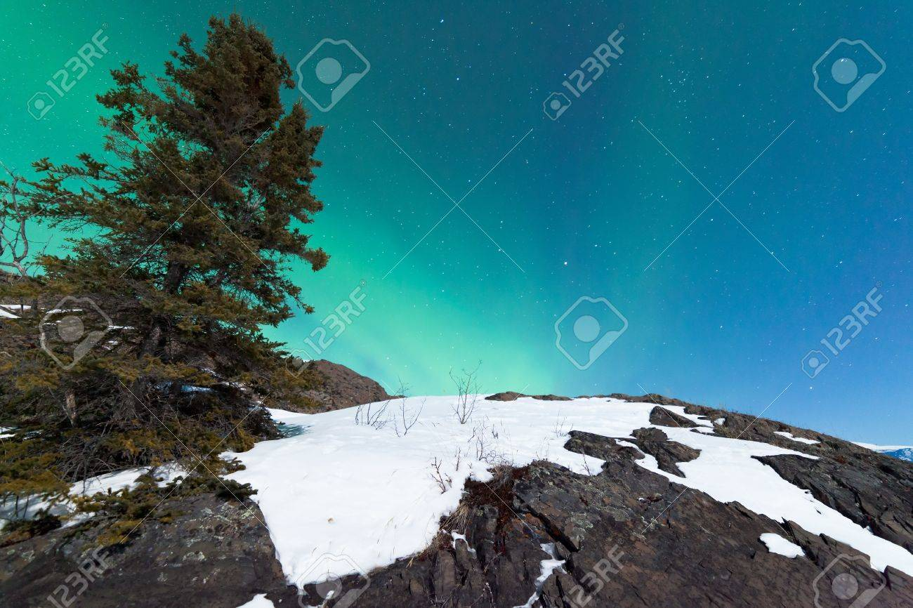 Northern Lights or Aurora borealis or polar lights forming green swirls over snowy rock outcrop in moon-lit winter night Stock Photo - 19220127