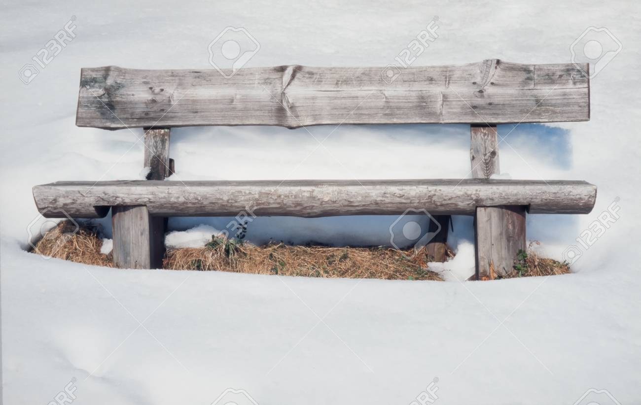 Vacant old rustic wooden bench standing in thick pristine white