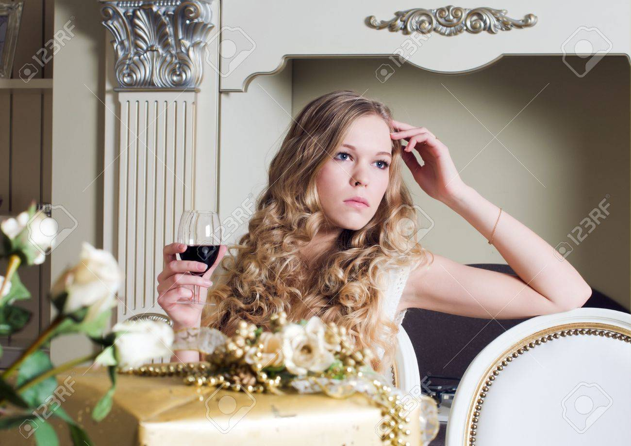 Portrait of the beautiful blonde. She is sitting with glass of red wine Stock Photo - 6490595