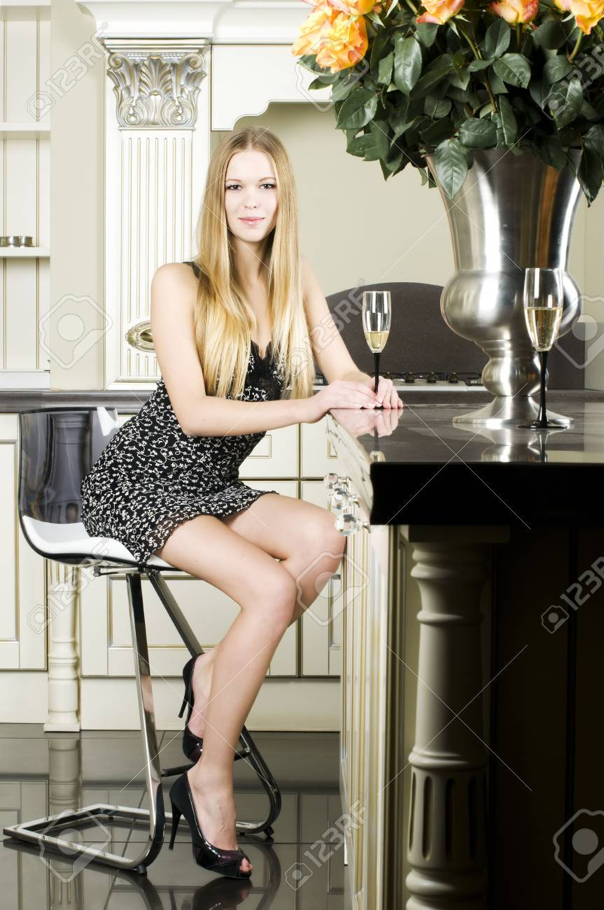 Portrait of the beautiful woman. She is sitting at her kitchen with glass of champagne Stock Photo - 7859778