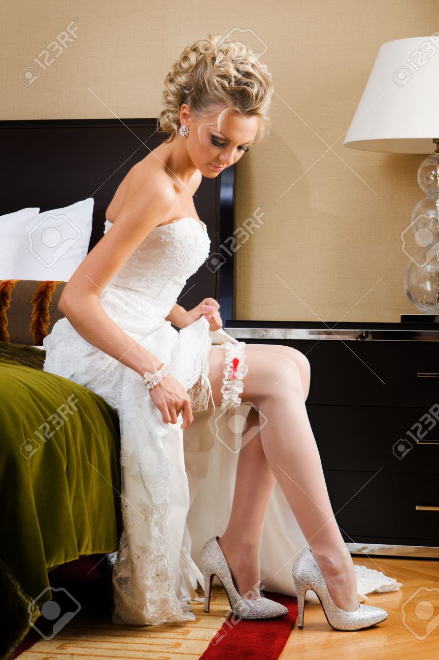 beautiful bride is sitting on the bed and trying the garter. Stock Photo - 11268831