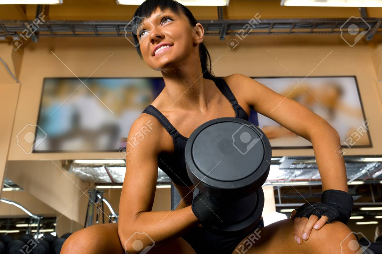 Beautiful woman is doing exercises with the bar  the sport club. Stock Photo - 12440093