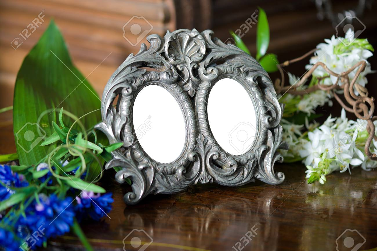 Still life with antique frame with woman's portrait  and flowers. Stock Photo - 12440212