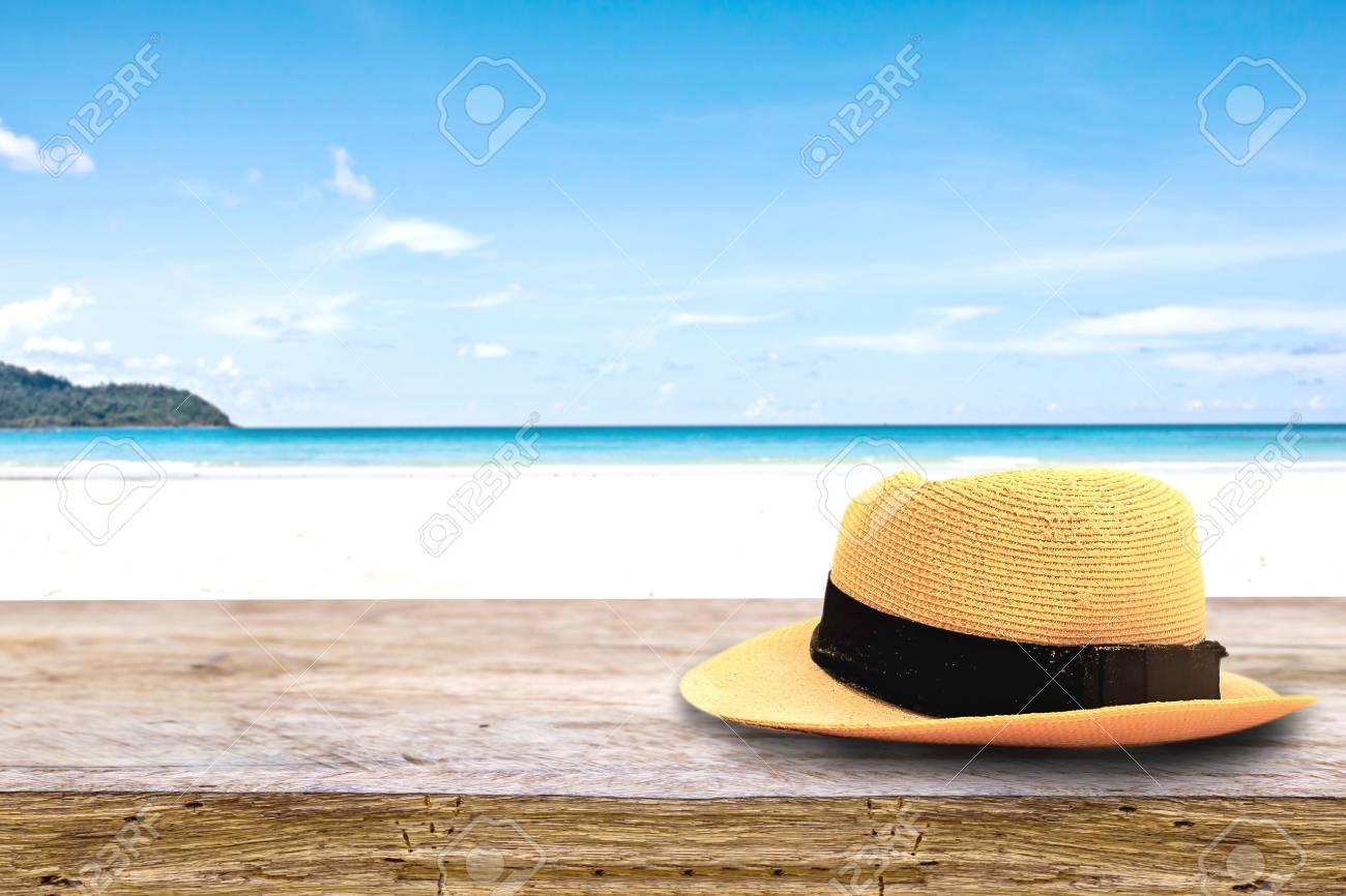 Beautiful Hat On On Wood Terrace Over Blue Sea And Tropical Island Beach Background.  Image For