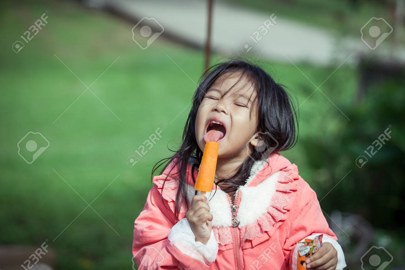 cute asian little girl is eating ice-cream in the park stock photo