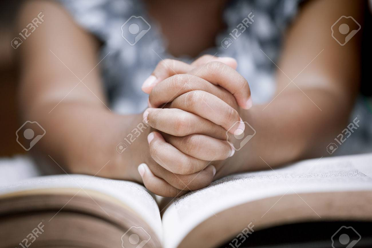 Little girl hands folded in prayer on a Holy Bible in church for faith concept in vintage color tone - 78416097